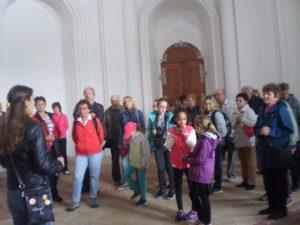 Rodáci poslouchají průvodkyni v Plasích